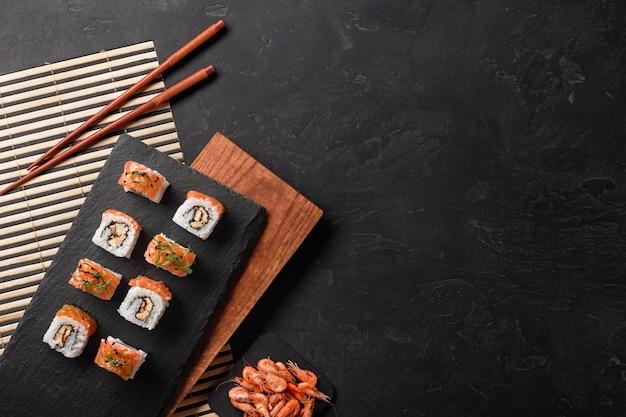 Conjunto de sushi e maki com uma garrafa de vinho na mesa de pedra.