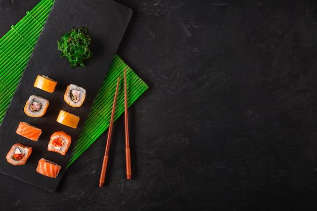 Conjunto de sushi e maki na mesa de pedra. vista superior com espaço para texto