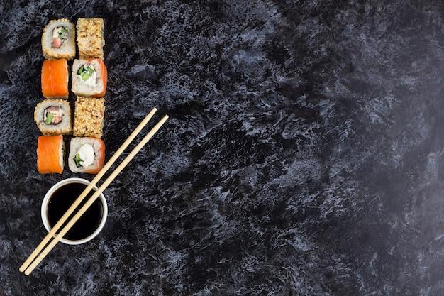 Conjunto de sushi e maki na mesa de pedra. vista superior com fundo de espaço de cópia