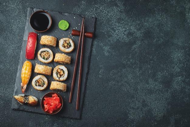 Conjunto de sushi e maki na mesa de pedra.