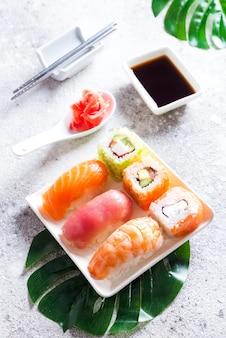 Conjunto de sushi e maki roll e folhas verdes palm na mesa de pedra.