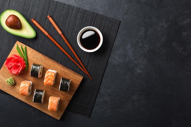 Conjunto de sushi e maki rolos com fatias de abacate na mesa de pedra. vista do topo.