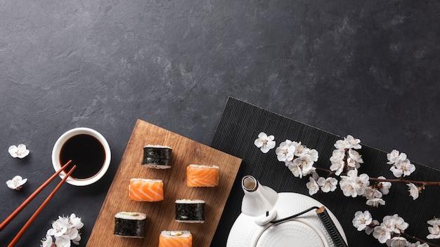 Conjunto de sushi e maki rolos com ramo de flores brancas e bule na mesa de pedra. vista do topo.