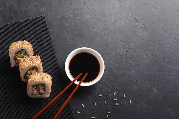 Conjunto de sushi e maki rolos com ramo de flores brancas na mesa de pedra. vista do topo.