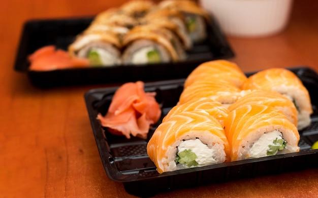 Conjunto de sushi em caixa de plástico com salmão, camarão, wasabi e gengibre. cozinha tradicional japonesa. conceito de serviço de entrega de comida.