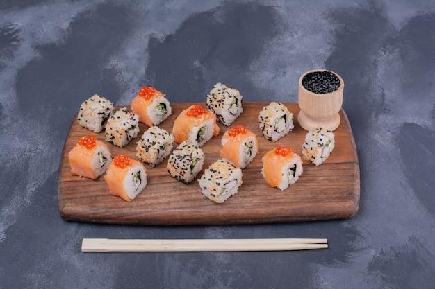 Conjunto de sushi. filadélfia e alaska rolam na placa de madeira com pauzinhos.