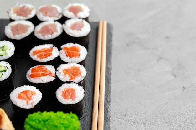 Conjunto de sushi maki servido em bandeja de pedra preta de perto