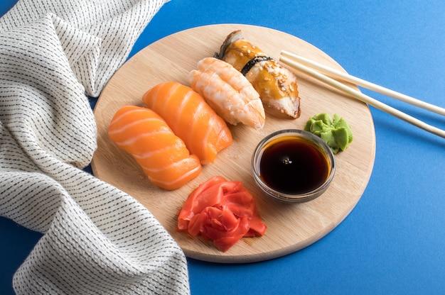 Conjunto de sushi nigiri apetitoso delicioso servido em placas de madeira com molho de soja e pauzinhos.