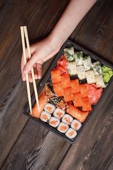 Conjunto de sushi rola delicadeza varas de madeira vista superior culinária japonesa. foto de alta qualidade