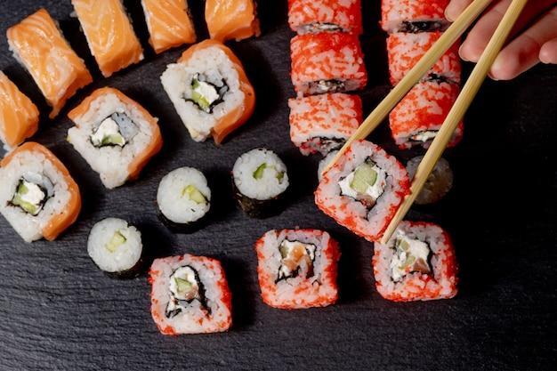 Conjunto de sushi roll on black slate background alimentos peixes filadélfia japonês salmão delicioso sushi arroz pepino refeição tradicional wasabi fresco saudável gourmet cozinha crua.