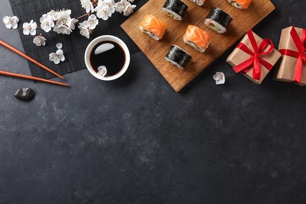 Conjunto de sushi, rolos de maki, caixas de presente com ramo de flores brancas na vista superior da mesa de pedra.