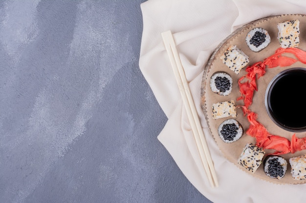 Conjunto de sushi. rolos de sushi maki e alaska na placa de madeira com toalha de mesa, gengibre em conserva e molho de soja.