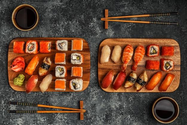 Conjunto de sushi: sushi e sushi rola na placa de madeira, vista superior.