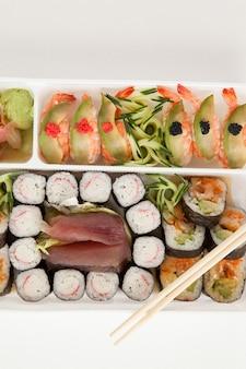 Conjunto de sushi variado servido com pauzinhos em caixa branca contra um fundo branco