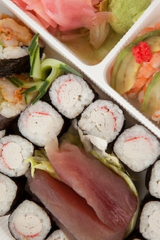 Conjunto de sushi variado servido em caixa branca contra fundo branco