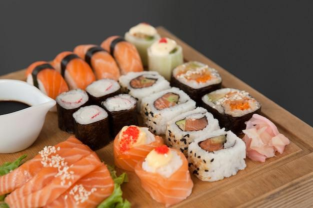 Conjunto de sushi variado servido na bandeja de madeira contra fundo preto