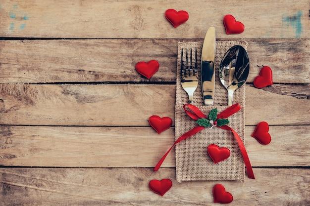 Conjunto de tabelas para celebração do dia dos namorados. configuração do lugar da mesa de madeira e talheres com coração vermelho para o dia dos namorados.