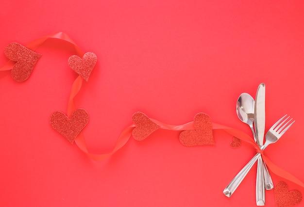 Conjunto de talheres com corações vermelhos
