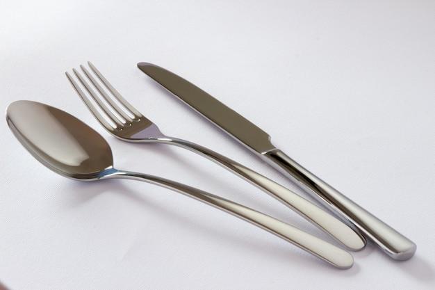 Conjunto de talheres com garfo, faca e colher isolado no fundo branco.