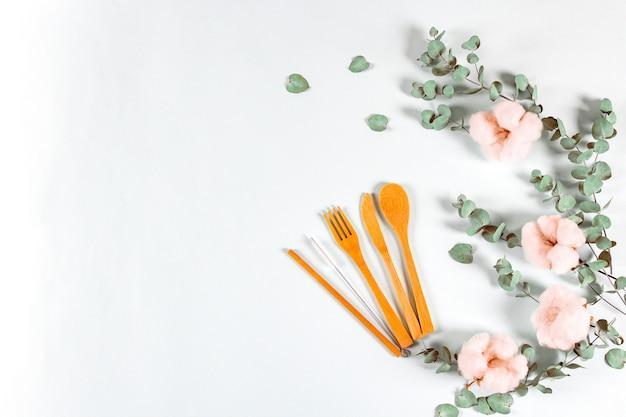 Conjunto de talheres de bambu amigável natural de eco, folhas de eucalipto e flores de algodão na luz de fundo.