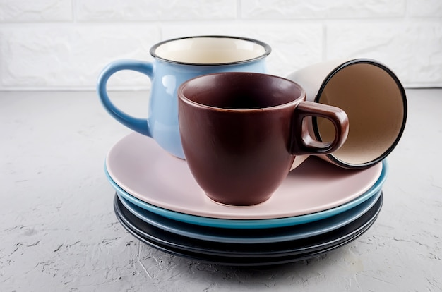Conjunto de talheres de louça de cerâmica limpa em fundo cinza de concreto, tigelas de cor, prato, copo,
