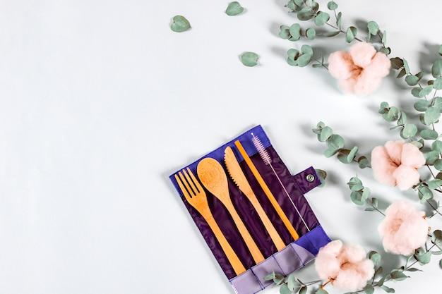 Conjunto de talheres de madeira natural eco em saco de saco, folhas de eucalipto e flores de algodão em fundo pastel.