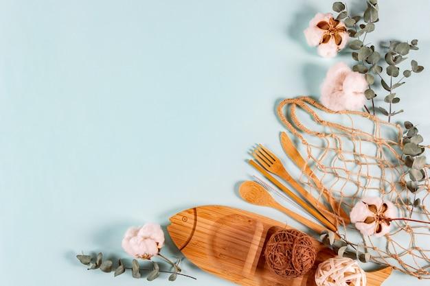 Conjunto de talheres de madeira natural eco, prato, malha de saco de corda, folhas de eucalipto e flores de algodão em fundo pastel.