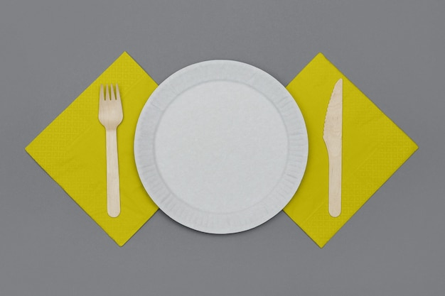 Conjunto de talheres descartáveis ecológicos de material natural. prato de papel branco, garfo e faca de madeira e guardanapos amarelos em fundo cinza, vista superior. conceito ecológico.