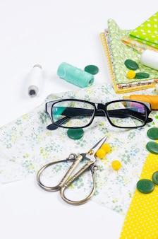 Conjunto de tecidos coloridos amarelos e verdes, tesouras, botões, carretéis de linha e óculos