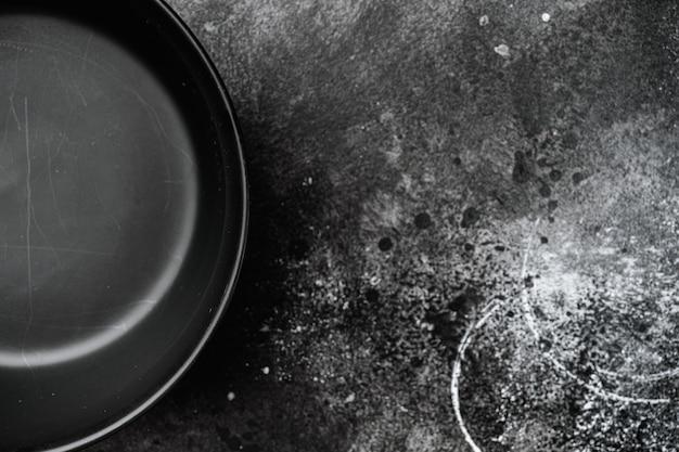 Conjunto de tigela de cerâmica preta, com espaço de cópia para texto ou comida, com espaço de cópia para texto ou comida, vista de cima plana lay, sobre fundo preto de mesa de pedra escura