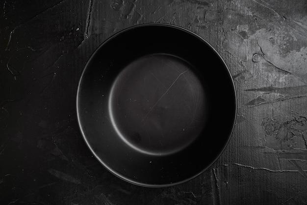 Conjunto de tigela preta, com espaço de cópia para texto ou comida, com espaço de cópia para texto ou comida, vista de cima plana lay, no fundo preto da mesa de pedra escura