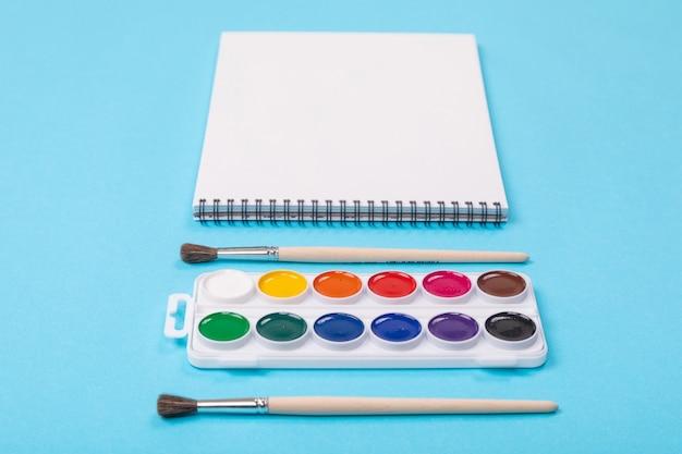 Conjunto de tintas aquarelle com pincéis e álbum para pintura isolado em fundo azul