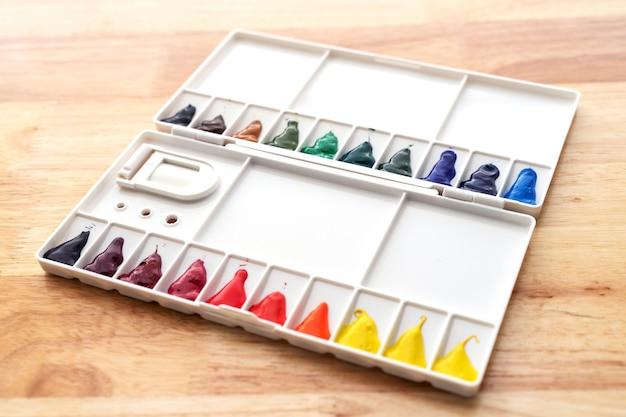 Conjunto de tintas em aquarela. cor na paleta aquarela suja em fundo de madeira. tintas aquarelas multicoloridas brilhantes em caixa de tinta.
