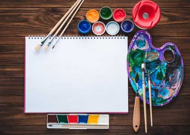 Conjunto de tintas, lápis, ferramentas para pintura e folha de papel branco em branco