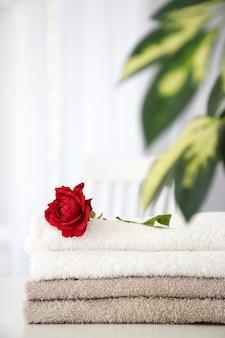 Conjunto de toalhas limpas de cor cinza e branca com rosa vermelha e folhas de scheflera na mesa branca. conceito de spa ou salão de massagem.