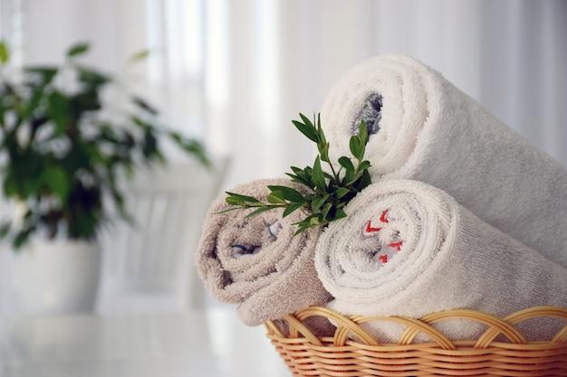 Conjunto de toalhas limpas enroladas em uma cesta de vime decorada com ervas verdes.