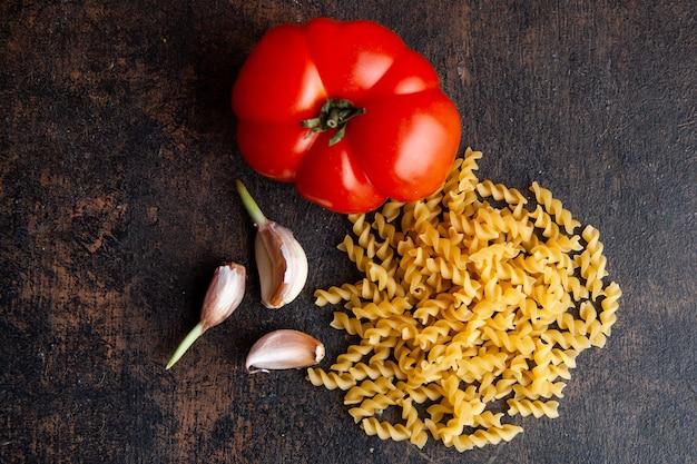 Conjunto de tomate e alho e macarrão em um plano de fundo texturizado escuro. vista do topo.
