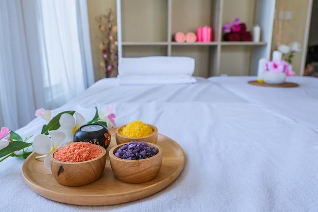 Conjunto de tratamento de spa e óleo de massagem aromática na massagem da cama. cenário tailandês para aromaterapia e massagem com flores na cama, relaxar e cuidados saudáveis.