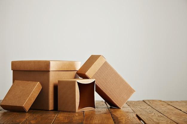Conjunto de três caixas de papelão artesanais semelhantes, sem etiqueta, com tampas lindamente dispostas em um estúdio com paredes brancas