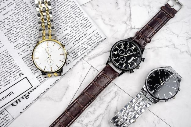 Conjunto de três novos relógios de pulso masculinos com pulseira de couro e aço inoxidável prateado e dourado. jornal com notícias de negócios em superfície de mármore