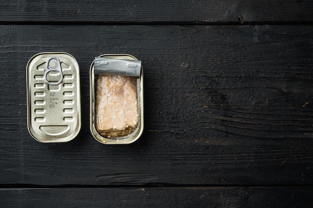 Conjunto de truta selvagem em lata, em lata, sobre mesa de madeira preta