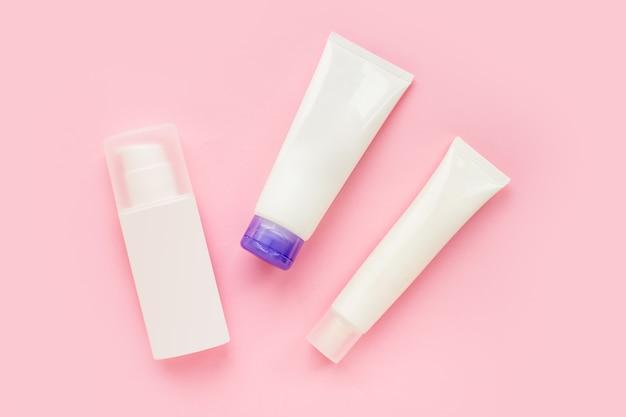Conjunto de tubos brancos de creme para cuidados com a pele do rosto isolado em fundo rosa, vista superior, maquete