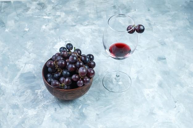 Conjunto de um copo de vinho e uvas pretas em uma tigela de barro sobre um fundo cinza sujo. vista de alto ângulo.