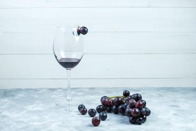 Conjunto de um copo de vinho e uvas pretas sobre fundo cinza e de madeira sujo. vista lateral.