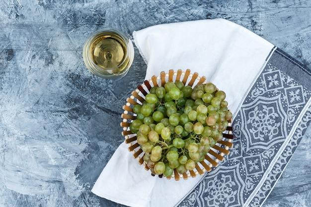 Conjunto de um copo de vinho e uvas verdes em uma cesta em gesso sujo e fundo de toalha de cozinha. vista do topo.