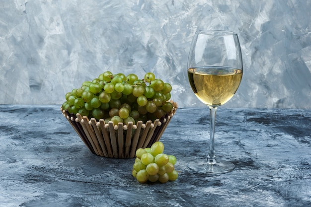 Conjunto de um copo de vinho e uvas verdes em uma cesta em um fundo de gesso sujo. vista lateral.
