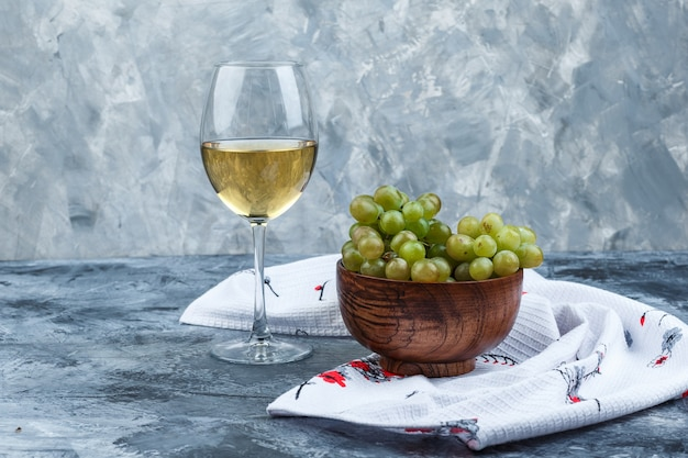 Conjunto de um copo de vinho e uvas verdes em uma tigela sobre fundo de gesso e toalha de cozinha sujo. vista lateral.