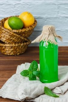 Conjunto de um pedaço de pano branco, folhas de limão e limão e suco em uma cesta sobre uma superfície de madeira. vista de alto ângulo. espaço para texto