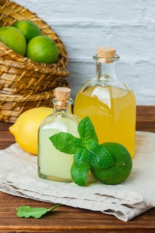 Conjunto de um pedaço de pano branco, folhas de limão e limão e suco em uma cesta sobre uma superfície de madeira. vista de alto ângulo.