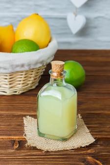 Conjunto de um pedaço de pano branco, limão e suco em uma cesta sobre uma superfície de madeira. vista de alto ângulo.